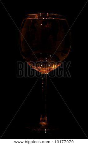 A glass of white wine, orange illuminated in the dark