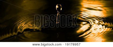 close up of a drop of water in golden tone