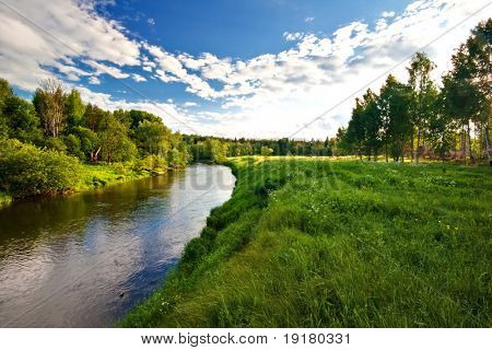 Green field with river under blue sky