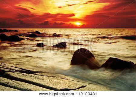 Tropical sunset on the stones beach. Phuket island. Thailand