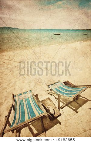 Two sun beach chairs on shore near sea in grunge and retro style