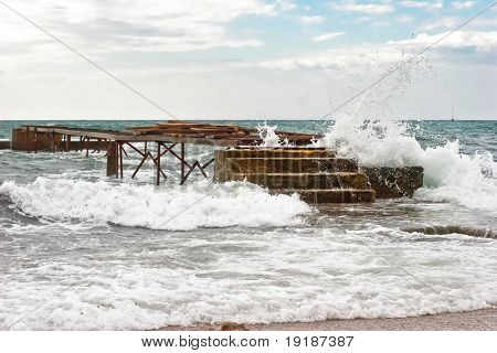 Old pier and stormy weather with breaking waves