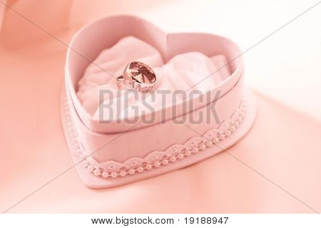 Two wedding ring in the heart shaped box in pink tones