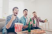Постер, плакат: Yes Winners Goal Cheerful Young Guys Are Watching Match On Couch At Home And Drink Beer Eat Pizz