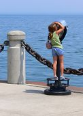 picture of burlington  - An little girl on an telescope looking over the lake Ontario on the lake