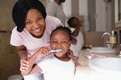 Portrait of smiling mother with daughter brushing teeth in bathroom at home poster