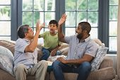 Multi-generation family giving high five while sitting together on couch at home poster