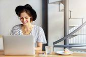 Pretty Young Female Copywriter Wearing Black Hat And Stripped Blouse Working On Laptop Computer, Loo poster