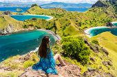 Rear view of a young woman enjoying the awesome view of Padar Island while sitting on the top of a v poster