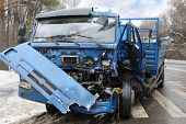 Damaged big truck after car accident with many damages on road at winter poster