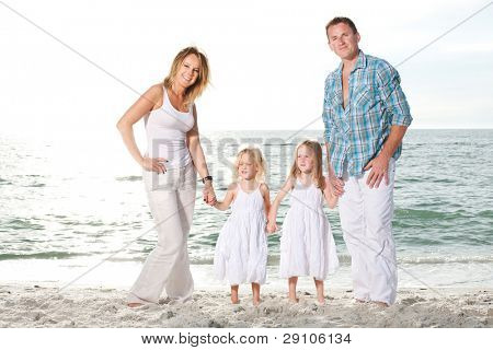 Beautiful young family enjoy sunny day at the beach.