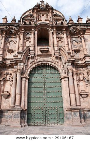 Female tourist at front of old door, Cuzco, Peru.