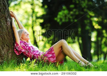 happy girl lying under a tree on a summer day