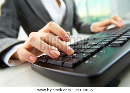 Macro image of human hand with forefinger going to press key on keyboard