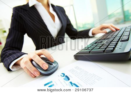 Image of female hands pushing keys of a computer mouse and keyboard with papers near by