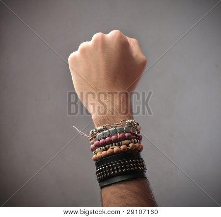Closeup of a man's arm full of bracelets