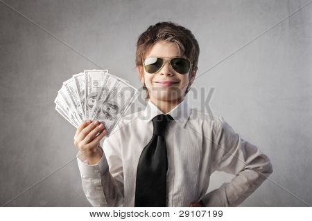 Child disguised as a rich businessman holding many banknotes