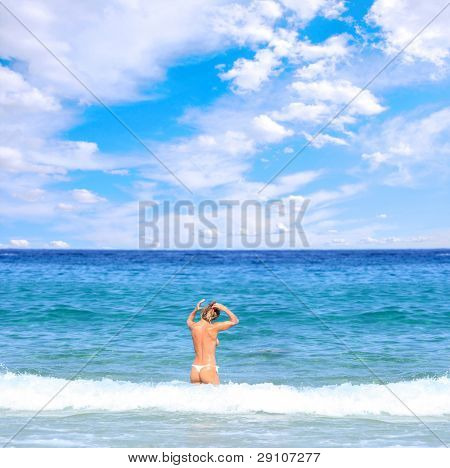 beautiful blonde topless woman in the sea  wearing white thong