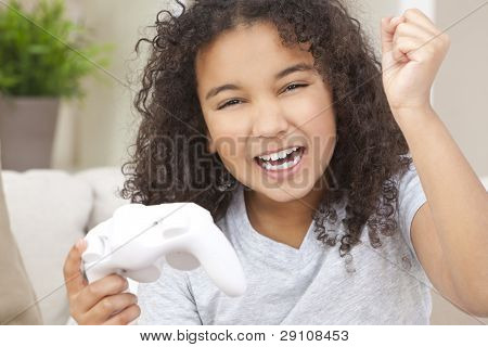 Beautiful young happy mixed race interracial African American girl child celebrating playing video games