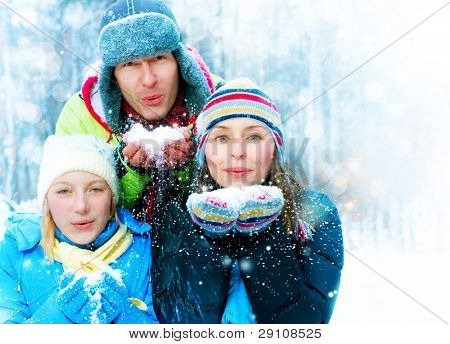 Family Outdoors.Happy Family with kid blowing Snow.Winter