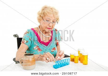 Senior woman in a wheelchair, couting out her pills for the week.  White background.