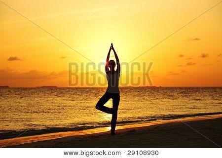 sunset yoga woman on sea coast