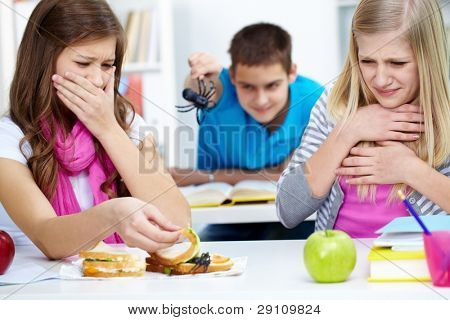 Two disgusted girls looking at spider in one of their sandwiches