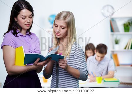 Portrait of teacher looking at her student copybook while explaining mistakes