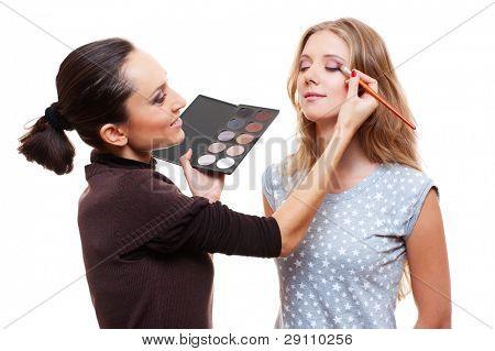 Maquilladora Profesional aplicar sombra de ojos. aislado sobre fondo blanco