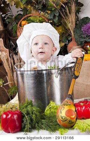 Menino bonito, vestindo um chapéu de Chef, sentado dentro de uma panela grande cozinha