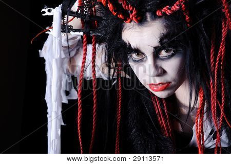 woman with voodoo shaman make-up isolated on black