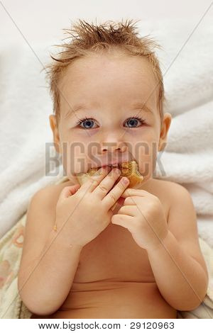 Close-up Portrait Of Funny Hungry Baby Boy Eating Fresh Bread