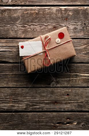 Vintage gift box (package) with address card on old wooden background.