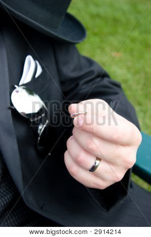 Groom With Black Tuxedo And Sunglasses Holding Wedding Ring