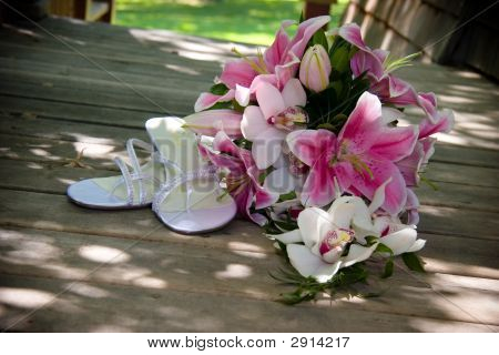 White Wedding Shoes And Bouquet Of Flowers