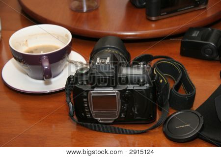 Cup Of Coffee With Dslr Digital Camera And Lens Cap