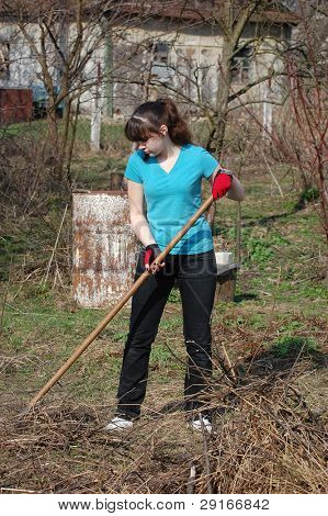 Teen girl work with rakes.Ukraine