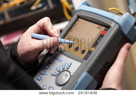 Network Technician Adjusting Reflectometer