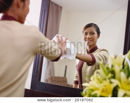 Asian Maid Working In Hotel Room And Smiling