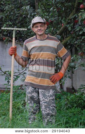 Man work with rakes. Ukraine
