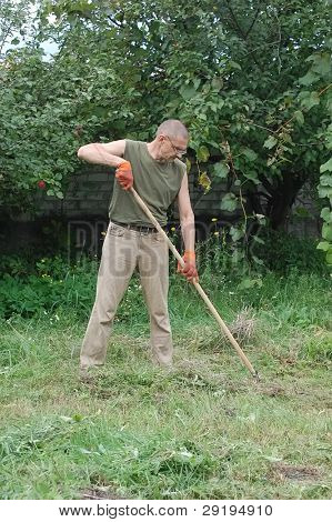 Man work with rakes. Ukraine