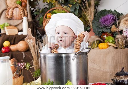 Portrait Of A Baby Wearing A Chef's Hat Sitting Inside A Large Cooking Stock Pot