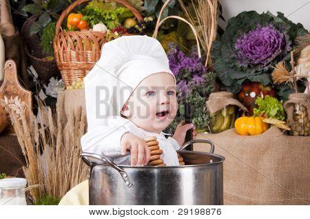 Retrato de um bebê usando chapéu um Chef sentado dentro de uma panela grande cozinha