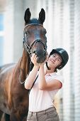 Smiling Cheerful Teenage Girl-equestrian Holding Funny Horse Snout. Colored Outdoors Vertical Summer poster