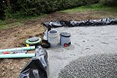 image of sand gravel  - Installing a sand and gravel filter for a domestic septic tank system showing the plastic liner for the trench with sand in position and a pile of gravel waiting to be spread after the upper pipes have been connected  - JPG