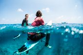 Young surfers sit on their surfboards in the tropical ocean, woman smiles and looks at the camera, m poster