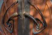 Old Wooden Entrance Door With Antique Door Handle Curls On The Front Door poster
