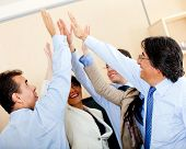 Successful business group giving a high-five at the office