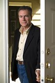 stock photo of front door  - A man entering through the front door with a smile on his face - JPG