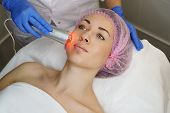 Hardware Cosmetology. Ultrasound Chromotherapy. Beautician Carries Out Procedure For Tightening Skin poster